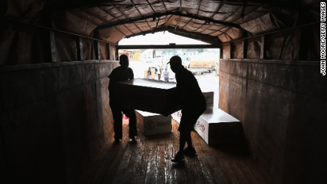 Workers unload medical supplies from a USAID cargo flight in Liberia in August.