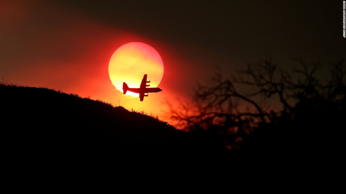 A firefighting air tanker flies in front of the setting sun while battling the Rocky Fire on August 1.