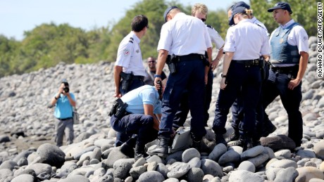 Caption:Police officers inspect metallic debris found on a beach in Saint-Denis on the French Reunion Island in the Indian Ocean on August 2, 2015, close to where a Boeing 777 wing part believed to belong to missing flight MH370 washed up last week. A piece of metal was found on La Reunion island, where a Boeing 777 wing part believed to belong to missing flight MH370 washed up last week, said a source close to the investigation. Investigators on the Indian Ocean island took the debris into evidence as part of their probe into the fate of Malaysia Airlines flight MH370, however nothing indicated the piece of metal came from an airplane, the source said. AFP PHOTO / RICHARD BOUHET (Photo credit should read RICHARD BOUHET/AFP/Getty Images)