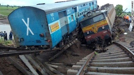 Two passenger trains lay next to each other following a derailment after being hit by flash floods on a bridge in Madhya Pradesh, India, on August 5, 2015.