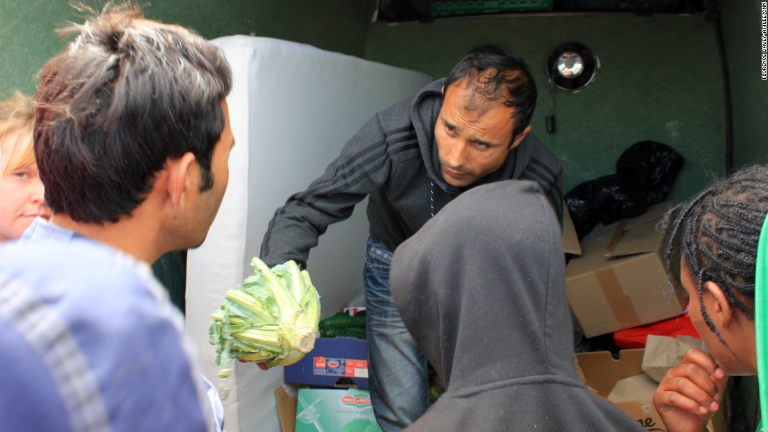 A local charity hands out food. People cover up their faces when the cameras are around because they don't want their families at home to see them in these conditions. Many people tell their families they are doing well in Europe.