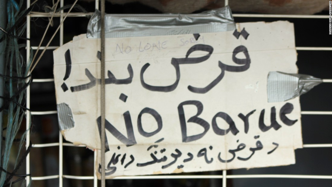 "A sign reads ""no credit"" in three languages. Shopkeepers don't give loans to customers who they know might be on a truck across the English Channel the next day."