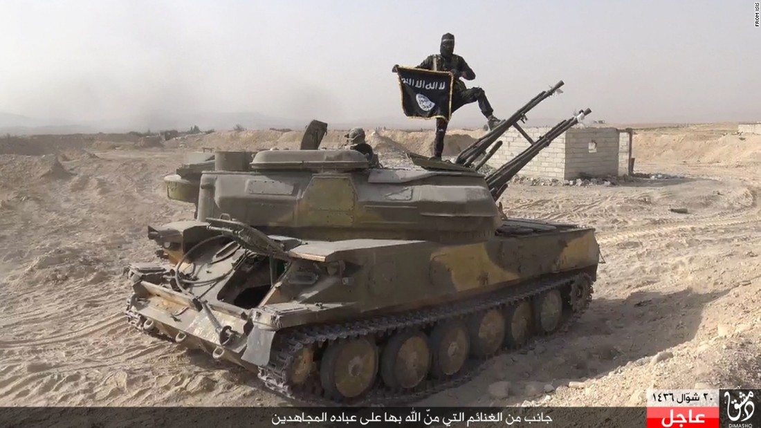 "In this image taken from social media, an ISIS fighter holds the group's flag as he stands on a purportedly captured tank after the militant group <a href=""http://www.cnn.com/2015/08/07/world/syria-isis-al-qaryatayn-christians/index.html"" target=""_blank"">overran the Syrian town of al-Qaryatayn</a> on Thursday, August 6, the London-based Syrian Observatory for Human Rights reported."