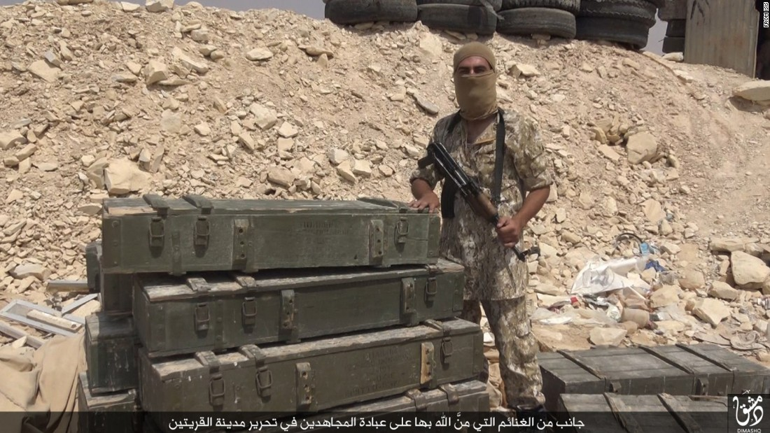 An ISIS fighter poses with spoils purportedly taken after capturing the Syrian town.