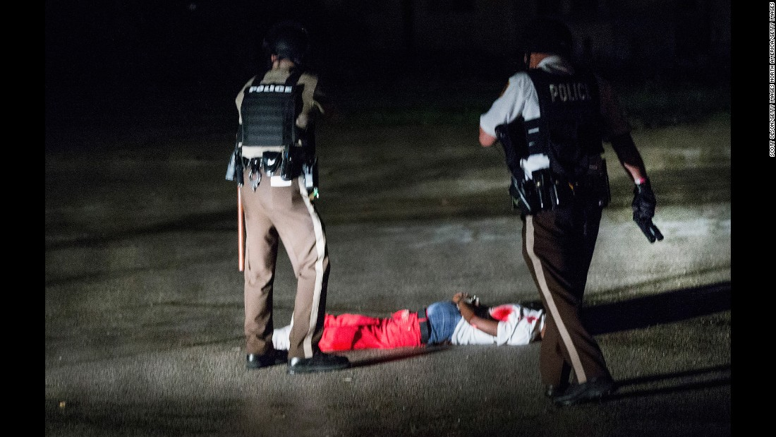 A man with gunshot wounds lies face down in a parking lot after a shootout with police in Ferguson on Sunday, August 9. Demonstrations started peacefully, but gunfire erupted Sunday night. Police say the man fired at them.
