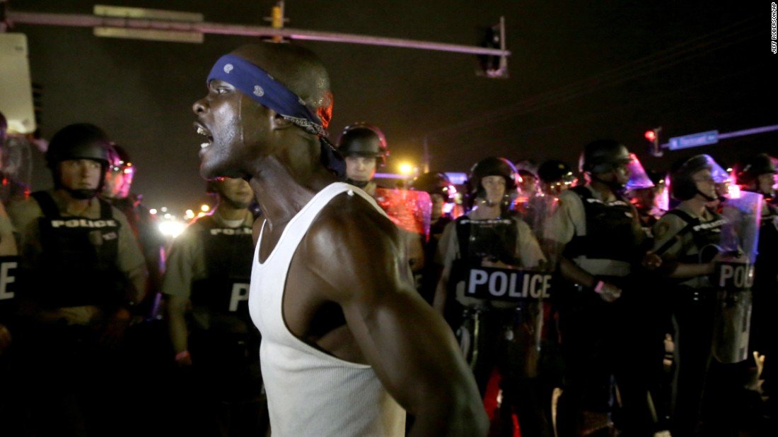 A protester yells in front of a line of police in Ferguson on August 9.