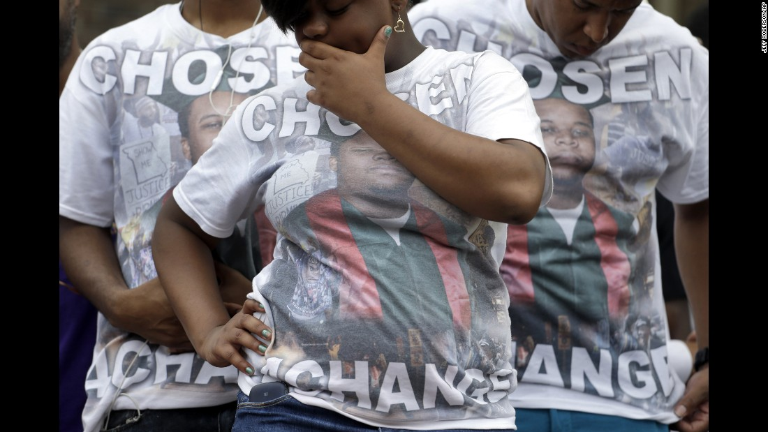 "Brown supporters wear T-shirts with the late teen's picture and the message ""Chosen 4 Change"" on August 9 as they take part in the remembrance ceremony in Ferguson."