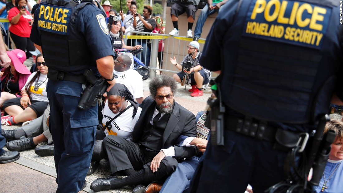 Cornel West, center, joins other protesters sitting on the steps of the Thomas F. Eagleton Federal Courthouse as members of the Federal Protective Service stand watch August 10 in St. Louis. Protesters have been arrested after blocking the entrance to the courthouse while calling for more aggressive U.S. government response to what they call racist law enforcement practices.