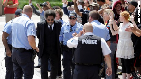 Cornel West is arrested by St. Louis Police during a protest outside the Thomas F. Eagleton Federal Courthouse, Monday, Aug. 10, 2015, in St. Louis. The arrests of scholar and civil rights activist West and the few dozen others were part of what's been billed as a national day of civil disobedience. (AP Photo/Jeff Roberson)