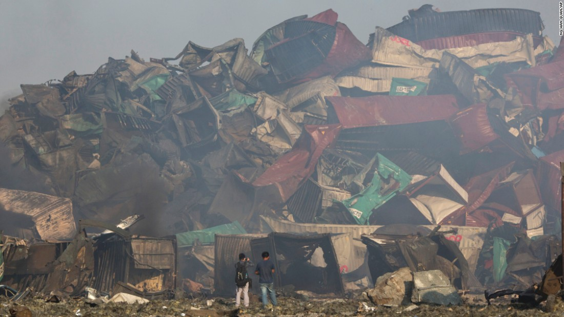 People walk among the crumpled remains of shipping containers. One of the explosions was estimated to be equivalent to 21 tons of TNT, or a magnitude-2.9 earthquake, according to the China Earthquake Networks Center.