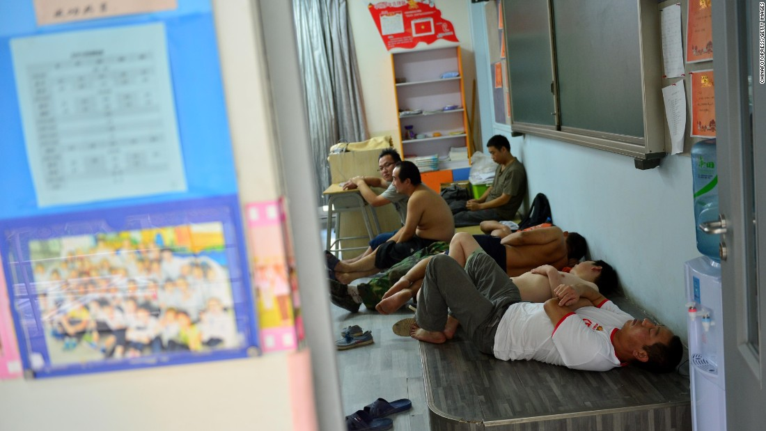 People sleep in a classroom at a primary school used as a makeshift emergency evacuation center.