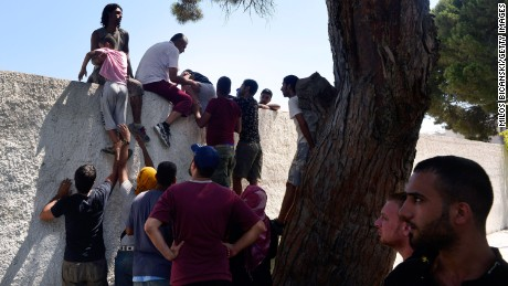 Migrants climb a wall of the national stadium where a registration exercise for the migrants was taking place on August 12.