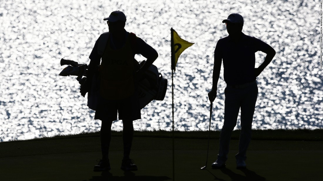 Bae Sang-Moon of South Korea waits with his caddy on the second green on Friday.