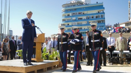 US Secretary of State John Kerry (L) watches as US Marines, stationed in Cuba, carry the American flag during the raising of the US flag over the newly reopened embassy in Havana, Cuba. Friday, Aug. 14, 2015. Cuba and US officially restored diplomatic relations July 20, as part of efforts to normalize ties between the former Cold War foes. AFP PHOTO/POOL/PABLO MARTINEZ MONSIVAISPABLO MARTINEZ MONSIVAIS/AFP/Getty Images