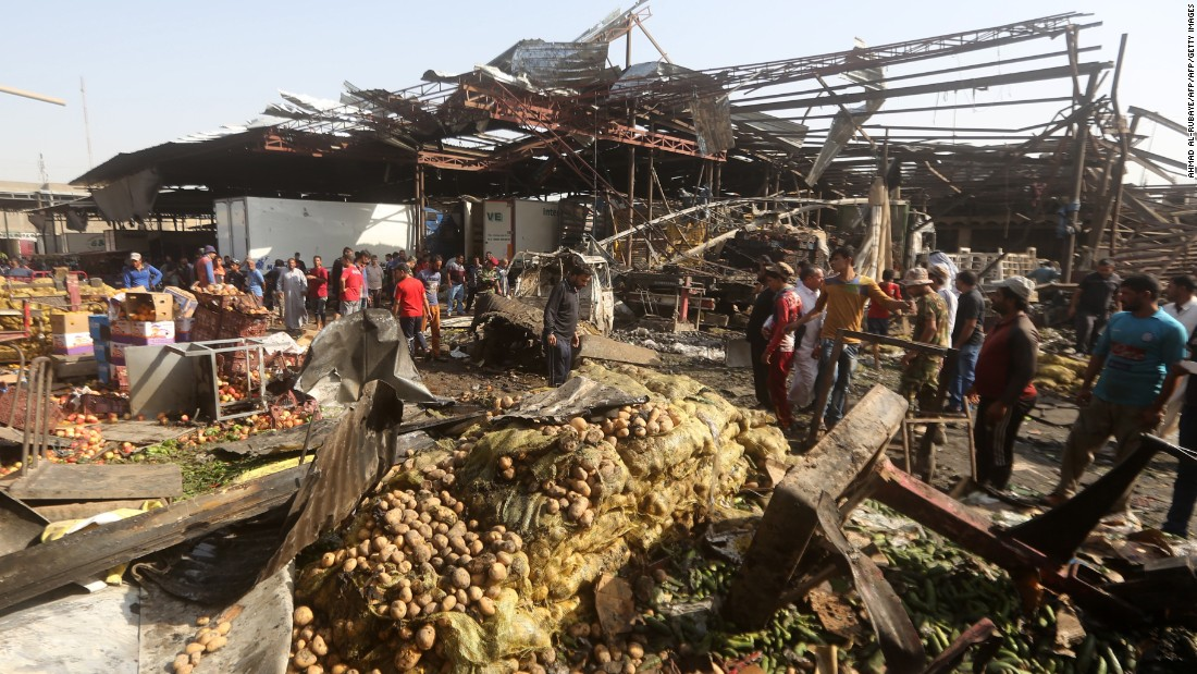 Iraqi men look at the damage following a bomb explosion that targeted a vegetable market in Baghdad's northern Shiite district of Sadr City on Thursday, August 13. ISIS claimed responsibility for the attack.