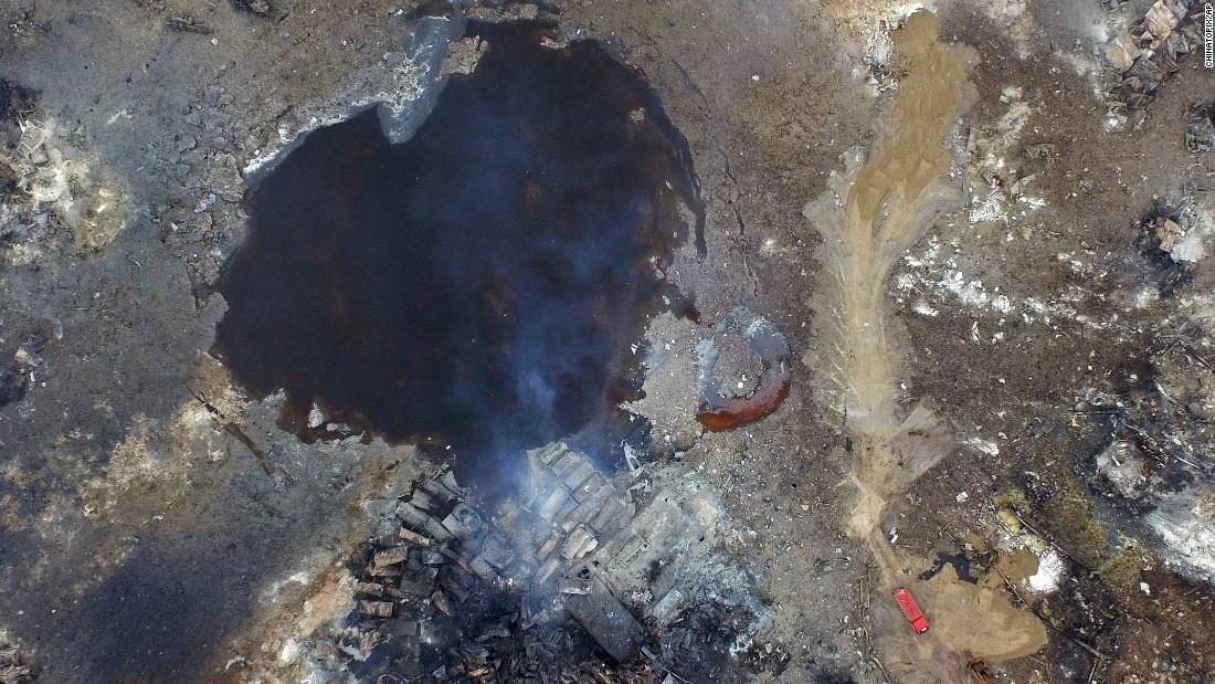 Smoke rises from debris on Saturday, August 15, near a crater that was at the center of a series of explosions in northeastern China's Tianjin municipality as seen from an aerial view.