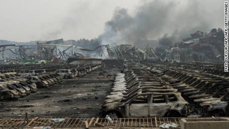 Smoke continues to billow from behind rows of burnt out Volkswagen cars the second morning after a series of explosions at a chemical warehouse hit the city of Tianjin, in northern China on August 14, 2015.  A Chinese military team of nuclear and chemical experts began work on August 14 at the site of two massive explosions in the city of Tianjin, state media said, as pressure grows for authorities to explain the cause of blasts that left 50 dead.    AFP PHOTO / FRED DUFOUR        (Photo credit should read FRED DUFOUR/AFP/Getty Images)