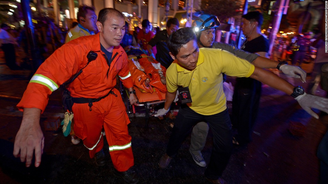 Rescue workers carry an injured person after a bomb exploded near a religious shrine in Bangkok, Thailand, on Monday, August 17.