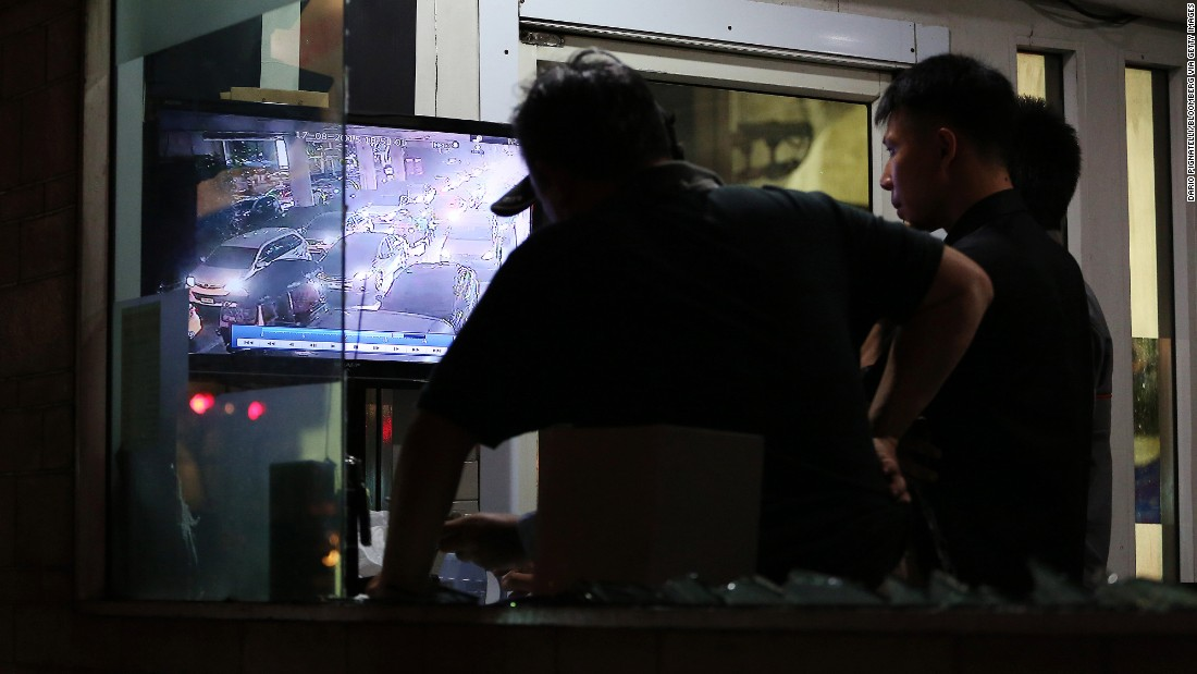 Police officers watch security video footage.