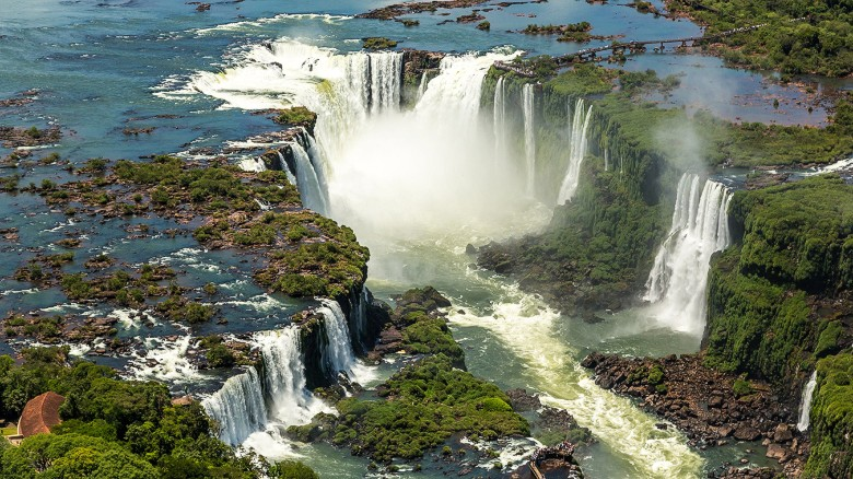 """A staggering spectacle of 275 waterfalls that cascade over more than a mile of the border between Brazil and Argentina, Iguazu's name translates as """"Big Water"""" -- a """"huge understatement"""" says LP."""