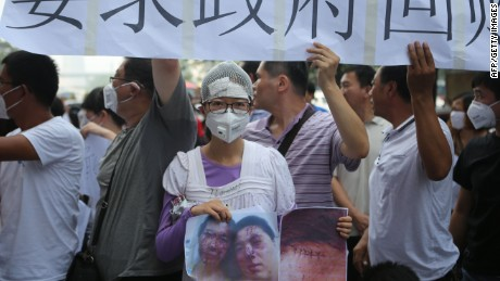 A resident injured by the explosions that hit a nearby chemical warehouse last week holds a photo of herself injured as she joins a protest outside the hotel where authorities are holding a press conferences in Tianjin on August 17, 2015. Rescuers at a Chinese industrial site where huge explosions killed at least 114 people combed through thousands of crushed shipping containers on August 17 in an effort to contain vast amounts of highly toxic cyanide, officials said, as state-run media lambasted authorities for their response to the tragedy. CHINA OUT AFP PHOTOSTR/AFP/Getty Images