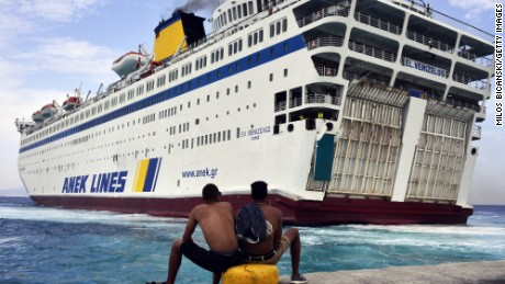 """KOS, GREECE - AUGUST 14: Two Syrian refugees sit at the dock of the port of Kos as the passenger ship """"Eleftherios Venizelos"""" backs into the quay on the Greek island of Kos, August 14, 2015. The Greek government is due to send a cruise ship to the island of Kos which will be able to carry up to 2,500 refugees and operate as a registration centre, after 2,000 Syrian refugees were locked in an old stadium during a registration process and left without water for more than a day. (Photo by Milos Bicanski/Getty Images)"""