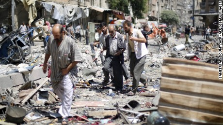 Syrians walk amid the rubble following air strikes by Syrian government forces on a marketplace in the rebel-held area of Douma, east of the capital Damascus, on August 16, 2015.