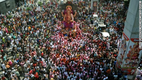 Indian Hindu devotees gather around a huge idol of the elephant-headed Hindu god Lord Ganesha during the procession for immersion into the Arabian Sea, on the streets of Mumbai on September 29, 2012.   During the ten-day Ganesh Festival Hindu devotees bring home idols of Lord Ganesha and offer prayers in temporary temples in order to invoke his blessings for wisdom and prosperity, culminating with the immersion of the idols in bodies of water, including the ocean.   AFP PHOTO/ Punit PARANJPE        (Photo credit should read PUNIT PARANJPE/AFP/Getty Images)