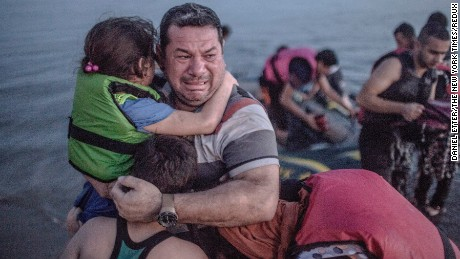A Syrian refugee from Deir Ezzor, holding his son and daughter, breaks out in tears of joy after arriving via a flimsy inflatable boat crammed with about 15 men, women and children on the shore of the island of Kos in Greece, Aug. 15,. The crossing from Bodrum, Turkey to Kos is so easy that the human tide has overwhelmed the island, leading its mayor, George Kiritsis, to predict that if he does not get help from Athens, blood will be shed.