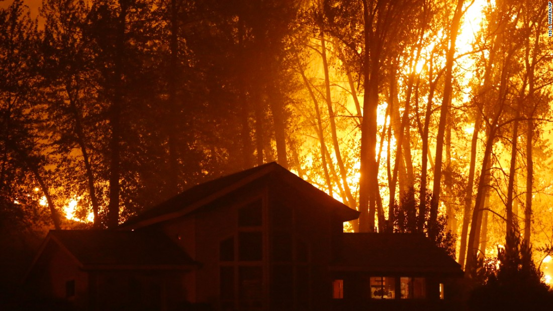 A wildfire burns behind a home in Twisp on August 20.