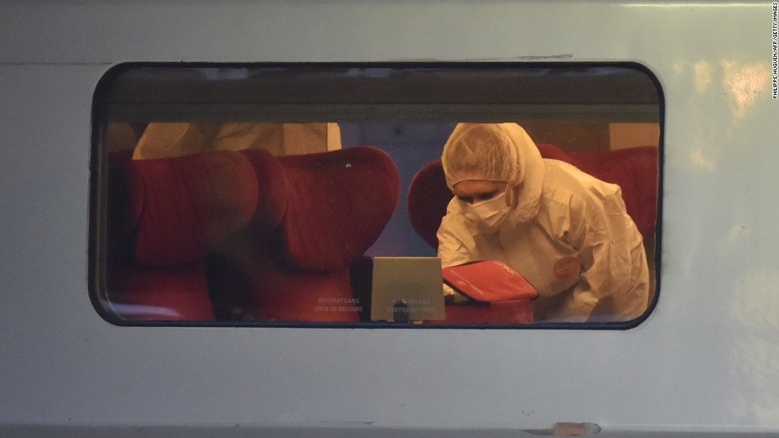 Police inspect the crime scene inside the train.