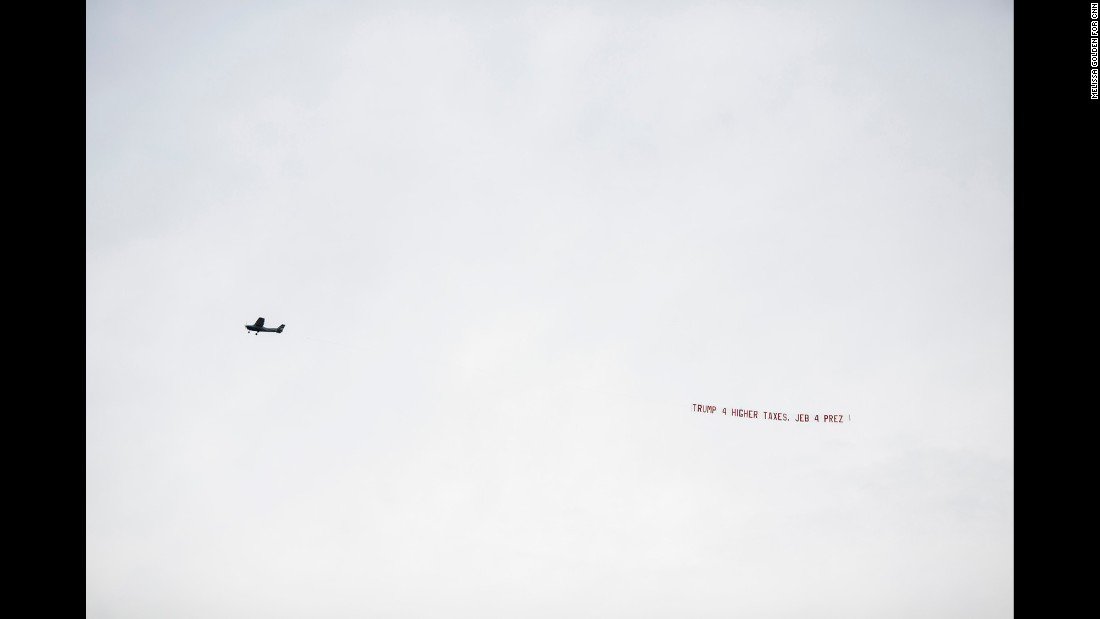 "A pro-Jeb Bush plane flies by the stadium with banner ""Trump 4 higher taxes. Jeb 4 Prez."" Bush's official campaign said it emailed supporters in Alabama pointing out Trump's previous liberal positions on abortion, gun rights and tax issues."