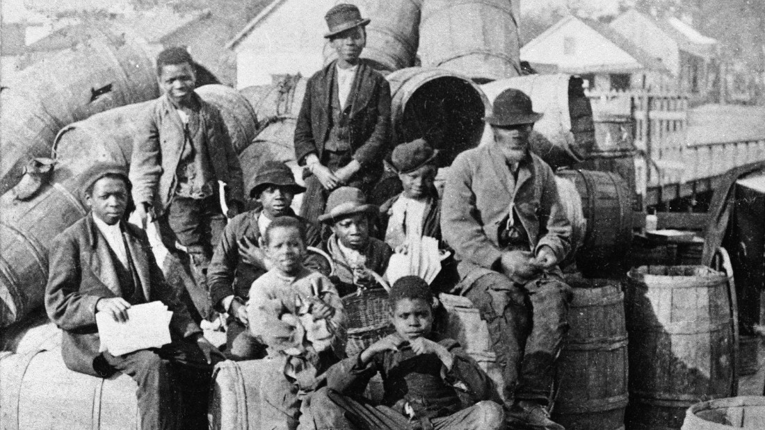 A group of men and boys, presumably slaves, sit on and around a pile of barrels on a pier or dock, Jacksonville, Florida, mid 19th Century. (Photo by C. Seaver Jr./Hulton Archive/Getty Images)