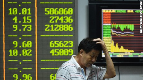 An investor gestures in front of screens showing share prices at a securities firm in Hangzhou, in eastern China's Zhejiang province on August 24, 2015.  Shanghai shares nosedived 8.49 percent on August 24 as Beijing's latest market intervention failed to restore confidence, with concern mounting about the stalling economy.