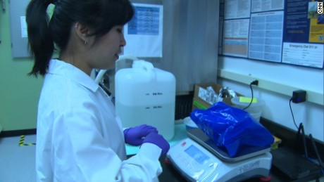 Christina Kim, a lab technician at OpenBiome, weighs Eric's poop donation.