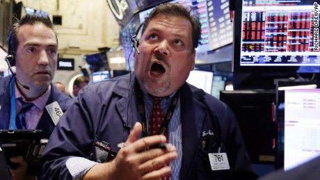 Trader John Santiago, center, works on the floor of the New York Stock Exchange on Monday, August 24.