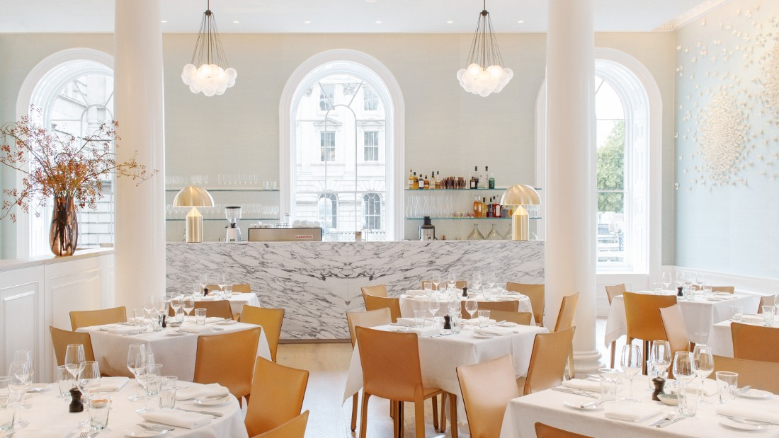 """Located in London's Somerset House, <a href=""""http://springrestaurant.co.uk/"""" target=""""_blank"""">Spring's</a> light-flooded drawing room is thanks to large arched windows, airy high ceilings. Original cornicing frames the space achieved by architect <a href=""""http://www.stuartforbes.com/"""" target=""""_blank"""">Stuart Forbes</a>. <br /><br />An atrium garden sits enclosed at the room's center with flora and fauna designs by landscape designer Jinny Blom. Other collaborators on the project include artwork by Emma Peascod and Valeria Nascimento and interior design by Australian Briony Fitzgerald."""