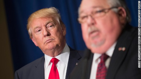 Republican presidential candidate Donald Trump listens as Sam Clovis speaks at a press conference at the Grand River Center on August 25, 2015 in Dubuque, Iowa. Clovis recently quit his position as Iowa campaign chairman for Rick Perry.