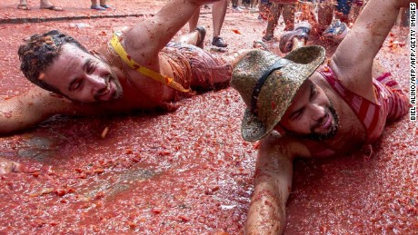 "Revellers mock a swim in tomato pulp during the annual ""tomatina"" festivities in the village of Bunol, near Valencia on August 26, 2015. Some 22,000 revellers hurled 150 tonnes of squashed tomatoes at each other drenching the streets in red in a gigantic Spanish food fight marking the 70th annual ""Tomatina"" battle.    AFP PHOTO / BIEL ALINO        (Photo credit should read BIEL ALINO/AFP/Getty Images)"