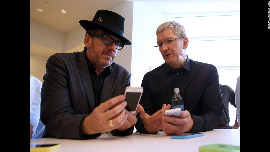 Musician Elvis Costello and Apple CEO Tim Cook with the new iPhone 5S at Apple's 2013 product announcement. The 5S featured a fingerprint sensor, an upgraded camera and an A7 processing chip.