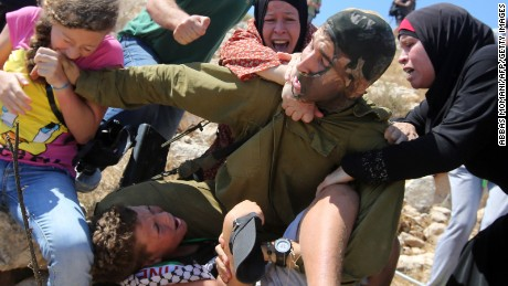 Women struggle to free the boy from the soldier.