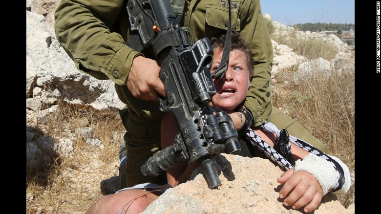An armed Israeli soldier attempts to to arrest an 11-year-old Palestinian boy with his arm in a cast on Friday, August 28, during a protest against settlement construction in the village of Nabi Saleh in the West Bank.