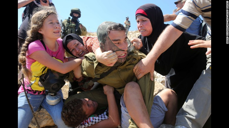 Women and children pull on the soldier's back, trying to free the boy.