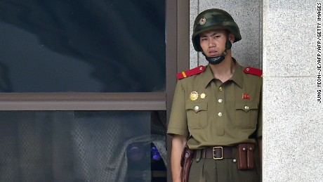 A North Korean soldier looks toward the South side while a group of foreign veterans who fought for South Korea during the 1950-53 Korean War and their relatives visit the truce village of Panmunjom in the Demilitarized Zone (DMZ) dividing the two Koreas on July 28, 2015. The veterans from Canada, the United States and Colombia were invited by a South Korean church group to mark the 62nd anniversary of the signing of an armistice accord that ended the war on July 27, 1953.      AFP PHOTO / JUNG YEON-JE        (Photo credit should read JUNG YEON-JE/AFP/Getty Images)