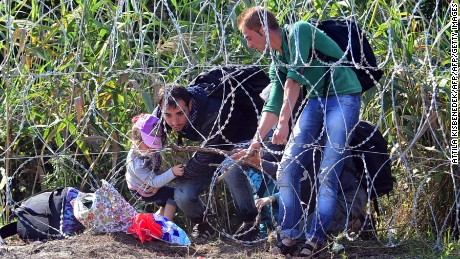 Migrants cross a border under the barbed fence near the village of Roszke on the Hungarian-Serbian border on August 28, 2015 . As Europe struggles with its worst migrant crisis since World War II, and Hungarian police has  so far this year intercepted some 141,500 migrants crossing into Hungary, mostly from neighboring Serbia.   AFP PHOTO / ATTILA KISBENEDEK        (Photo credit should read ATTILA KISBENEDEK/AFP/Getty Images)