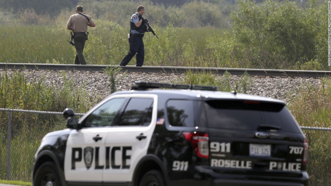 Police officers patrol a swampy area in Fox Lake.