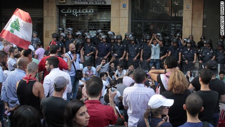 """Lebanese activists stand in front of riot police outside the environment ministry in downtown Beirut on September 1, 2015 as Lebanese police started forcefully evacuating protesters who had occupied part of the building in a surprise sit-in to demand the minister's resignation after mass protests which began over a nationwide trash collection crisis. A security source said police were gradually moving the several dozen protesters from the """"You Stink"""" campaign down from the seventh floor of the building. AFP PHOTO / STRSTR/AFP/Getty Images"""