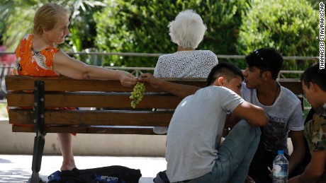 A local resident offers grapes to an Afghan migrant as they sit at Victoria square, Athens, Wednesday, Sept. 2, 2015, where many migrants stay temporarily before continuing their trip to more prosperous European countries. The country has borne the brunt of a massive refugee and migration flow of people heading into the European Union, with more than 200,000 people arriving so far this year.
