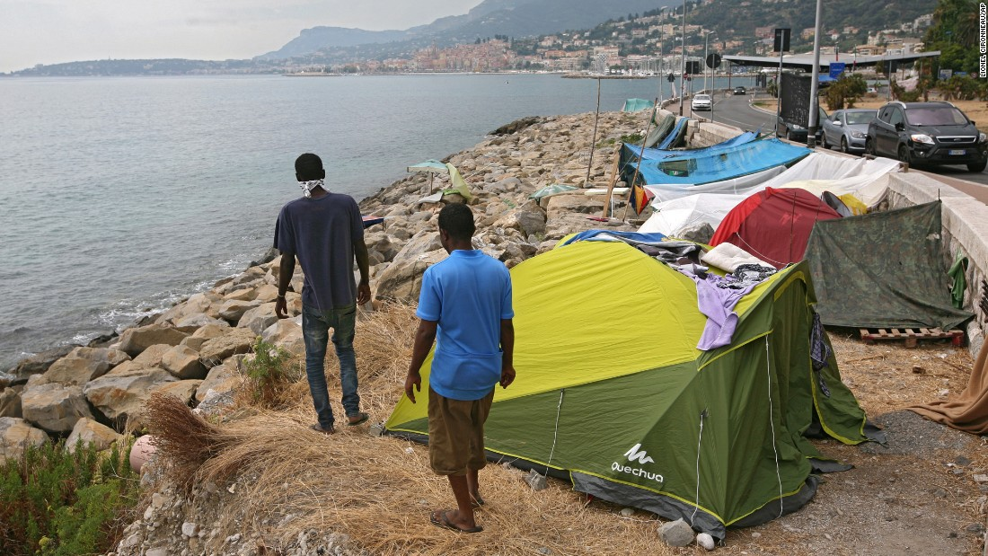 Migrants walk on a rocky beach in Ventimiglia, Italy, where they set up camp near the French border.