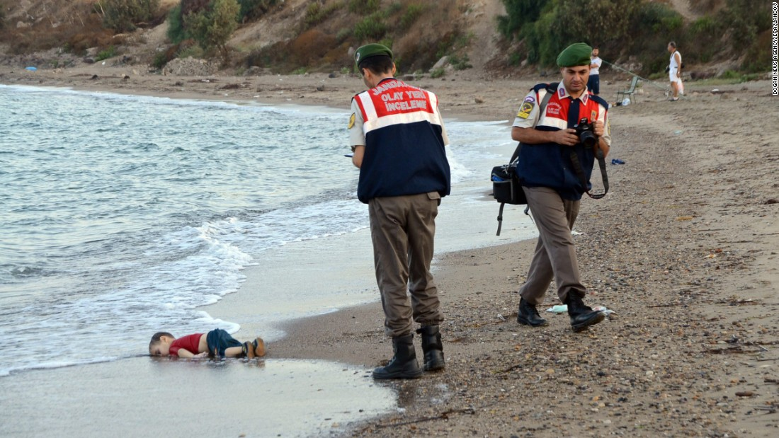 "Authorities stand near Aylan's lifeless body on Wednesday, September 2. This photo went viral around the world, often with a Turkish hashtag that means ""Flotsam of Humanity."""